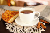Kopp te med halsduk på bord i rummet — Stockfoto