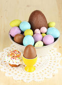 Composition of Easter and chocolate eggs and simnel on wooden table close-up — Stock Photo