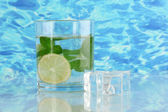 Glass of water with ice, mint and lime on sea background — Stock Photo