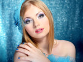 Portrait of beautiful young woman with glamour make up, on blue background — Стоковое фото