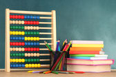 Toy abacus, books and pencils on table, on school desk background — Stock Photo