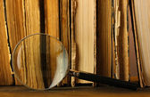 Magnifying glass and books on table — Stock Photo