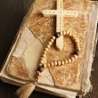 Bible, rosary and cross on wooden table close-up — Стоковая фотография