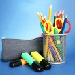 Pencil box with school equipment on blue background - Zdjcie stockowe