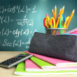 Back to school - blackboard with pencil-box and school equipment on table - 