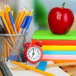 School supplies with apple and clock on wooden table — Stock Photo