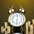 Alarm clock with coins on dark background — Foto Stock