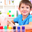 Cute little boy painting clay vase - Stock Photo