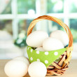 Many eggs in basket on table in room - Stock Photo