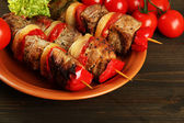 Tasty grilled meat and vegetables on skewer on plate, on wooden table — Stock Photo
