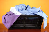 Parlak renkli arka plan üzerinde çamaşır sepeti giysilerle — Stok fotoğraf