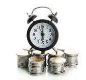 Reloj despertador con monedas aislado en blanco — Foto de Stock