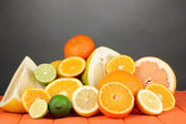 Lots ripe citrus on wooden table on black background — Stock Photo