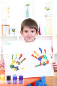 Cute little boy with his colorful handprint — Стоковое фото