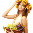 Beautiful young woman with yellow autumn wreath and grapes in basket, isolated on white — Stock Photo #19624257