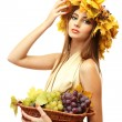 Beautiful young woman with yellow autumn wreath and grapes in basket, isolated on white — Stock Photo