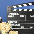 Movie clapperboard, cola and popcorn on blue background — Photo