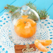 Tangerine on saucer under glass cover on blue background — Stock Photo