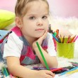Cute little girl playing with multicolor pencils, on blue background — Stok fotoğraf