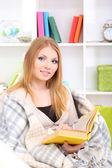 Attraktiv ung kvinna sitter på soffan och läsa bok, på hem inredning bakgrund — Stockfoto