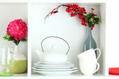 Beautiful white shelves with tableware and decor — Stock Photo