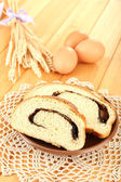 Loaf with poppy seeds on color plate, on wooden background — Stock Photo