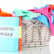 Clothes with washing powder in wooden basket isolated on white — Foto Stock #19694775