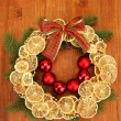 Christmas wreath of dried lemons with fir tree and balls, on wooden background — Stock Photo