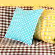Colorful pillows on couch on yellow background — Stock Photo #19697795
