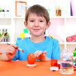 Cute little boy painting easter eggs — Stock Photo