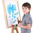 Little boy painting paints picture on easel isolated on white — Stock Photo