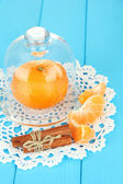 Tangerine on saucer under glass cover on blue background — 图库照片