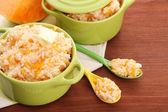 Taste rice porridge with pumpkin in saucepans on wooden background — ストック写真