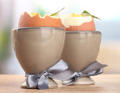 Boiled eggs in egg cups, on wooden table — Stock Photo