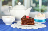 Teapot, cup of tea and delicious cake on window background — Foto Stock
