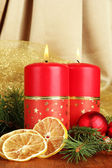 Two candles and christmas decorations, on golden cloth background — ストック写真