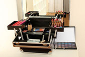 Open case with cosmetics on table near mirror — Stock Photo