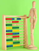Bright toy abacus and wooden dummy, on green background — Stock Photo