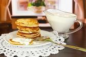Doces panquecas na chapa com creme de leite na mesa no quarto — Foto Stock