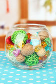 Dried oranges, wicker balls and other home decorations in glass bowl, on bright background — Stock Photo