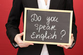 Young woman holding sign Do you speak english? — Stock Photo