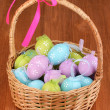 Stock Photo: Colorful easter eggs in basket on wooden background