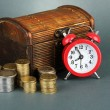Foto Stock: Alarm clock with coins in chest on grey background