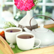 Cups of tea with flower and teapot on wooden tray on table in room — Stock Photo