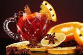 Perfumado vinho quente no vidro com especiarias e laranjas ao redor em fundo vermelho — Foto Stock