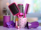 Hair brushes, hairdryer and cosmetic bottles in beauty salon — Stock Photo