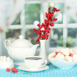 Beautiful white dinner service with an air meringues on blue tablecloth on window background — Stock Photo