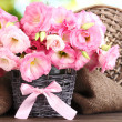 Stock Photo: Bouquet of eustomflowers in wicker vase, on wooden table, on green background