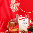 Cookies for Santa: Conceptual image of ginger cookies, milk and christmas decoration on red background — Stock Photo