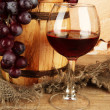 Composition of wine and grapes on wooden barrel on table on brick wall background — Stock Photo